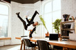 Young caucasian businessman having fun dancing break dance in the modern office at work time with gadgets. Management, freedom, professional occupation, alternative way of working. Loves his job.