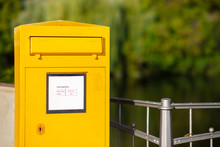 A Yellow Postal Mailbox In Germany In Front Of A Railing. Text Translation In The Picture: Times Of Emptying, Monday, Friday, Saturday.