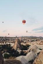 Hot Air Balloons Flying Over Mountains, Cappadocia, Turkey