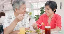 Elder Couple Eating In Restaur...