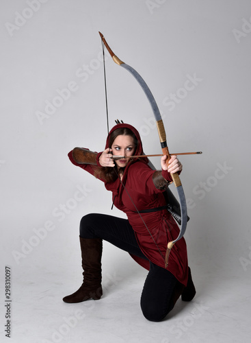 full length portrait of a brunette girl wearing a red fantasy tunic with hood, holding a bow and arrow Wallpaper Mural
