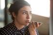 Leinwandbild Motiv Indian woman recording audio message or using voice recognition