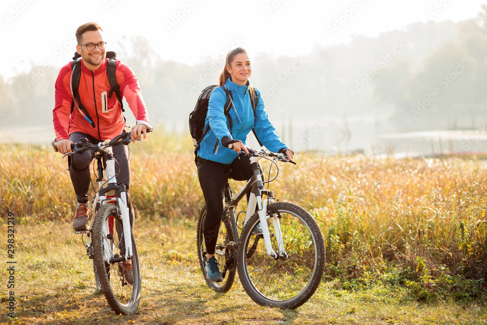 Fototapeta Beautiful happy young couple enjoying early morning bicycle ride by the river or lake. Sunrise through the mist above water in the background