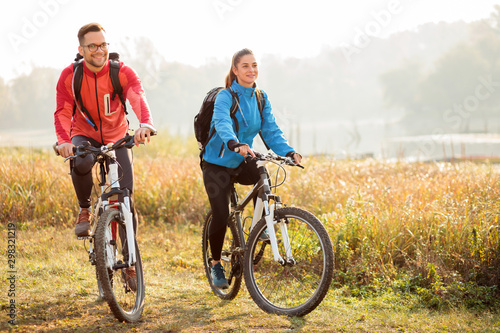 Fotografia Beautiful happy young couple enjoying early morning bicycle ride by the river or lake