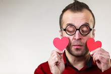 Sad Man Holding Two Red Hearts.