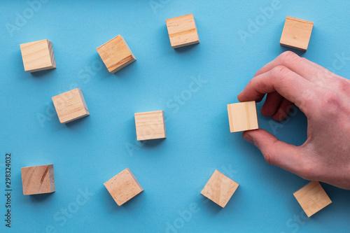 Hand choosing a wooden block from a set. Business choice concept Wallpaper Mural