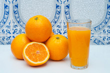 Glass Of Fresh Orange Juice And Oranges On The Light Ornamental Background. Healthy Food. Morning Ritual.