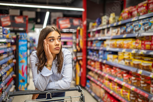 Fotografía  Young woman staying confused in grocery store
