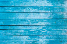 The Background Is Turquoise And The Color Of Old Painted Wooden Boards. Wooden Background Blue With Peeling Paint From Long Boards Arranged Horizontally