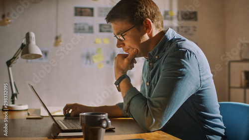 Fotomural  Professional Creative Man Sitting at His Desk in Home Office Studio Working on a Laptop and Thinking