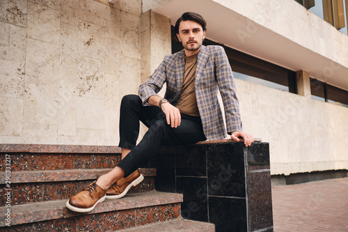 Valokuva Young handsome man in checkered jacket confidently looking in camera outdoor