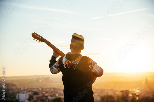 Young boy playing guitar in the city of Madrid, Spain in the background. - 298334492