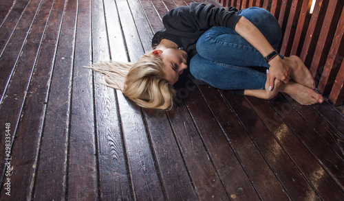Fototapeta young blonde woman lies on the dark wooden floor in a fetal position, her arms wrapped around her legs