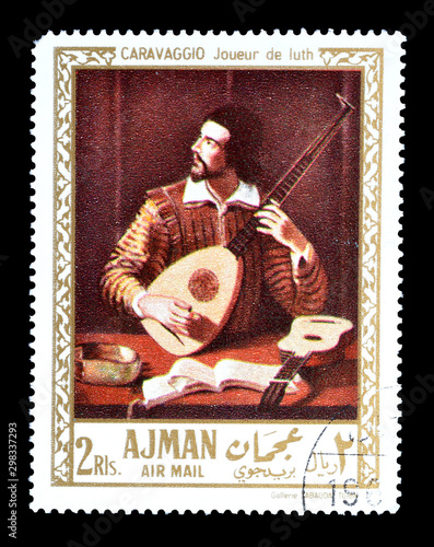 Fotografie, Obraz Cancelled postage stamp printed by Ajman, that shows Painting Portrait of man with the lute by Caravaggio, circa 1971