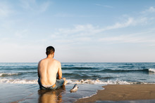 Back View Of Young Man Sitting At Seafront Beside A Caught Fish
