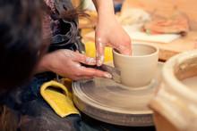 Potter In Workshop Working On Potters Wheel