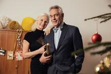 Senior Couple Holding Bottle Of Champagne On New Yera's Eve