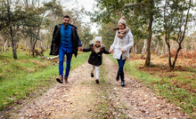 Happy Parents With Daughter Walking On Forest Path