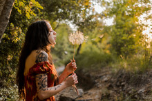 Young Woman Blows A Big Dandelion In A Forest At Sunset