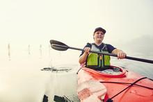 A Young Man Kayaker Paddles Th...