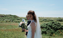 Portrait Of Bride And Groom Smiling Walking On A Summers Day