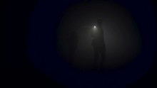 A Lonely Man Exploring Deep Dark Cave. Stock Footage. Silhouette Of A Person Standing Inside Of The Cave On The Background Of The Mystical Moonlit.