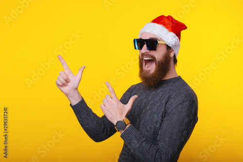 Fotografía  Screaming young handsome bearded man wearing santa claus hat and sunglasses poin