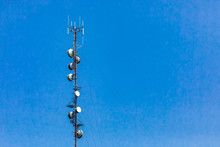 A Low Angle View Of A Tall Thin Cell Site Lattice Tower. Antenna And Satellite Equipment Used In 4G And 5G Data Exchange, Associated With EMF Pollution.
