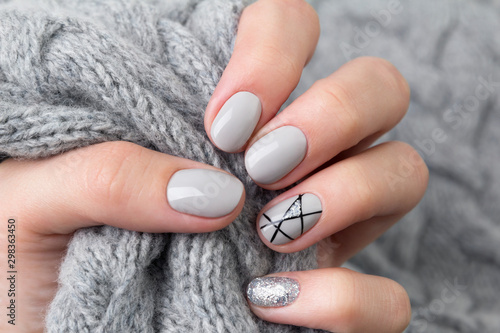Leinwand Poster Females hand with modern manicure holds gray knitted sweater  close up