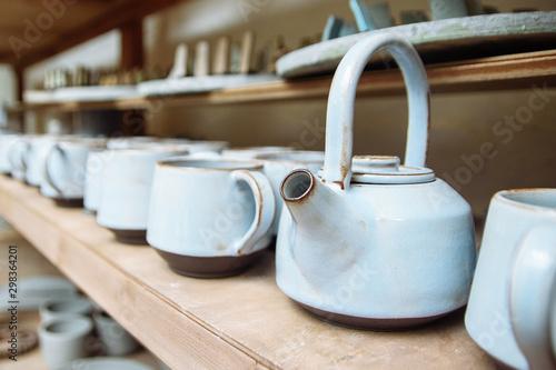Handmade ceramic teapots on a shelf in the master's workshop Wallpaper Mural