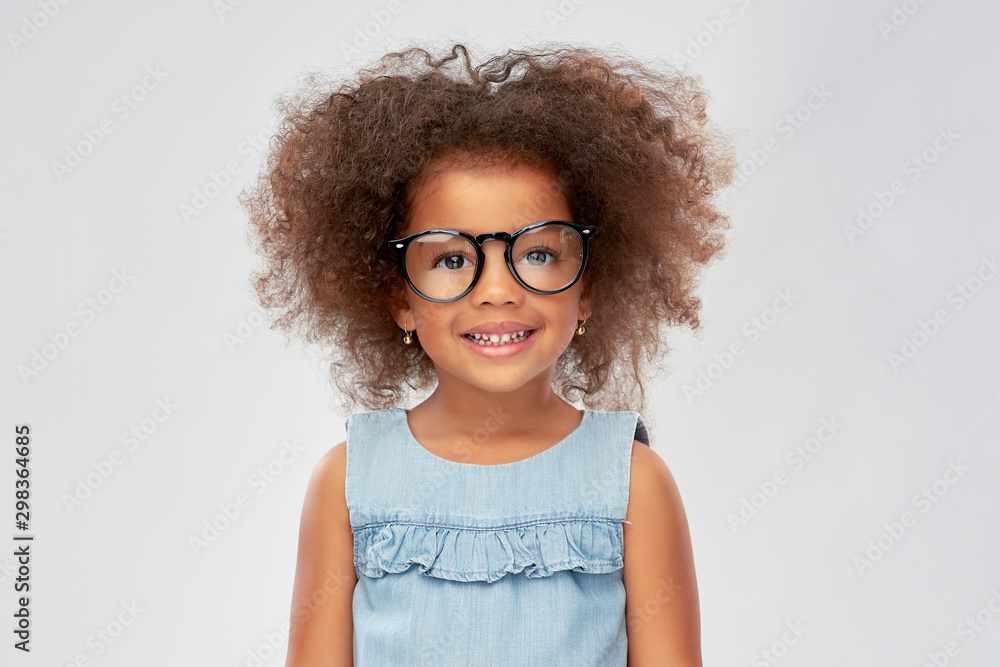 Fototapeta childhood, school and education concept - happy little african american girl in glasses over grey background