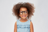 childhood, school and education concept - happy little african american girl in glasses over grey background