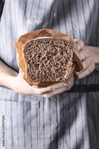 Trzymanie bochenka chleba w dłoniach na szarym tle w stylu rustykalnym