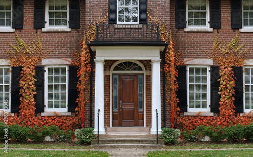 Fototapeta Traditional two story brick house with colorful ivy in fall. obraz