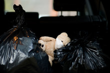 A Teddy Bear In A Protective Medical Bandage Lies On Garbage Bags In The Trunk Of A Car