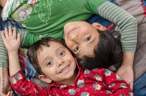 hermanos sonriendo en su cama con pijama, felicidad y sonrisas Canvas Print