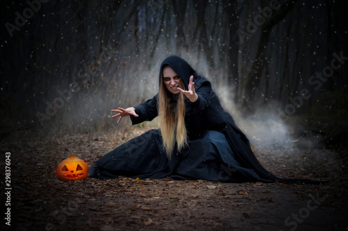 Pretty blonde in a witch costume for Halloween. Fotobehang