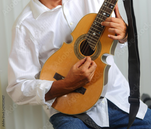 Photo A man with a white shirt playing a Puerto Rican Cuatro - Puerto Rico national string instrument