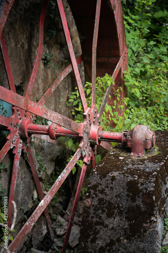 Canvas-taulu red Water wheel and gristmill with foliage and vines