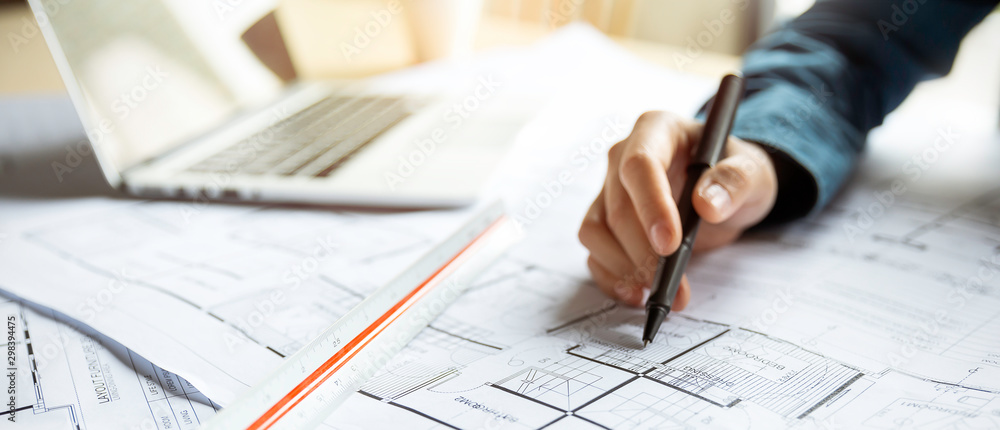 Fototapeta Close up woman hand working of Architect sketching project on blueprint at site construction work. Concept of architect, engineer in the office desk construction project banner