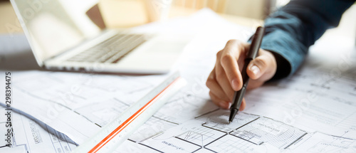 Close up woman hand working of Architect sketching project on blueprint at site construction work. Concept of architect, engineer in the office desk construction project banner