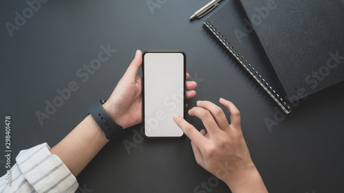 Fényképezés  Top view of young businesswoman touching blank screen smartphone in dark luxury