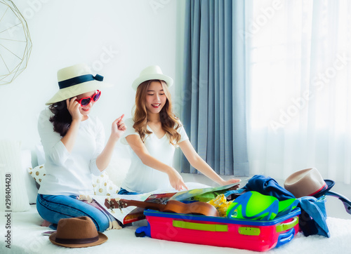 Photo  beautyful asian woman sits on a bed with a luggage with clothes and travel accessories