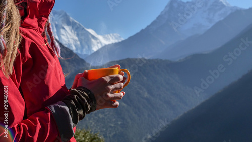 Fototapeta  Woman with cup of hot drink, enjoying the view, looking at Himalaya mountains landscape