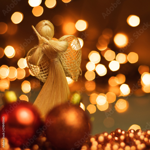 Christmas ornaments and straw angel lying on balls of a Christmas chain on a blurred background with lights. - 298410065