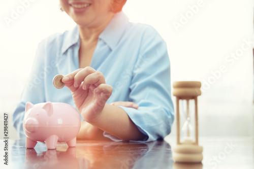 Fotomural  hand putting coin money to piggy bank saving, Close up