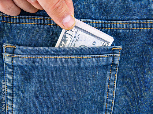 A hand takes money out of the back pocket of jeans. Canvas Print
