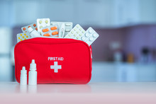 Medical First Aid Kit With Medicine And Pills On Table At Home