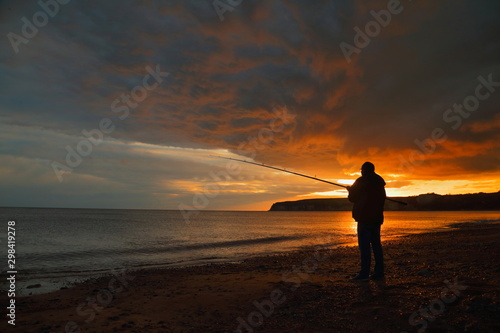 Fototapeten See sonnenuntergang Fly fishing at sunset on the Jurassic Coast in Devon
