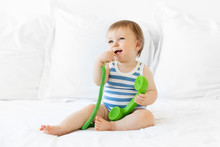 Cute Smiling Baby Sitting On Bed Chewing On Green Phone